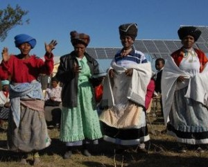 4 women standing in front of solar panels
