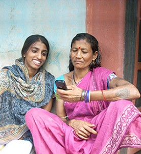Two women in India looking at a mobile phone