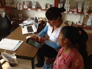 Two women sit together using an iPad