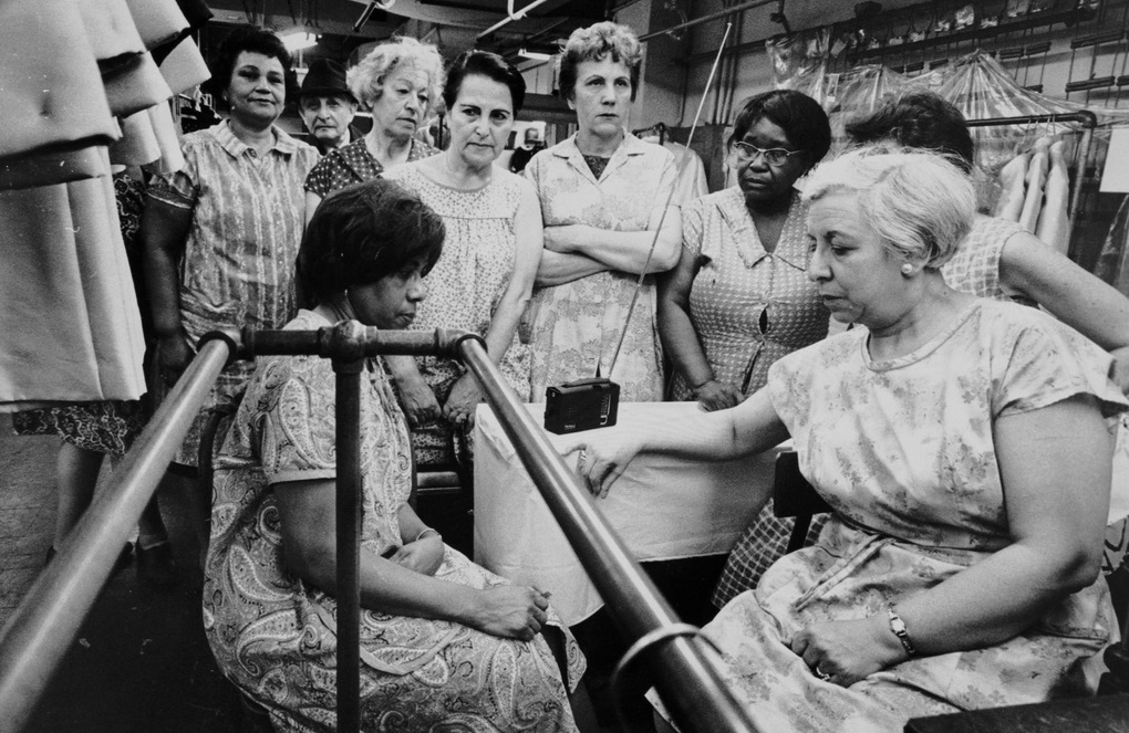 Garment workers listen to the funeral service for Martin Luther King Jr. on a portable radio – April 8, 1968