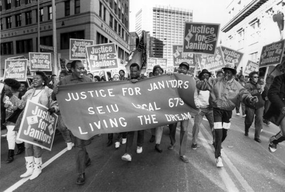 "Participants walk with a banner stating, ""Justice for Janitors - SEIU Local 679 - Living the Dream"" during the 1989 Martin Luther King, Jr. Day march in Atlanta, Georgia.  PHOTO: © Judy Ondry,  Courtesy of The Walter P. Reuther Library, Wayne State University"