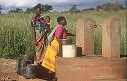 Two women and baby at a well