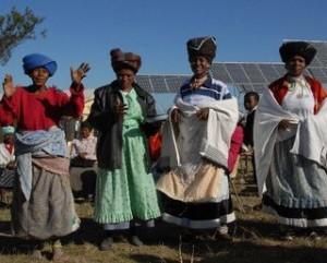 4 women standing in front of solar panels