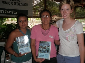 Kelly Quinn delivers copies of Donde no hay Doctor to 2 health promoters in Nicaragua.