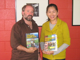 Jeff Conant and Oyungerel Tsedevamba hold Mongolian and English copies of Environmental Helath Book
