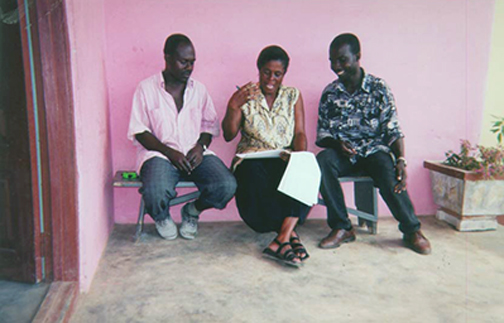 A woman is reading Hesperian material to 2 men