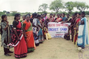 "A group of women surrounding a sign that reads ""Cricket Camp"""