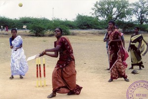 A woman holding a bat looks in the air as a ball comes towards her.