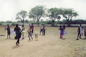 A woman running the bases in a cricket game.