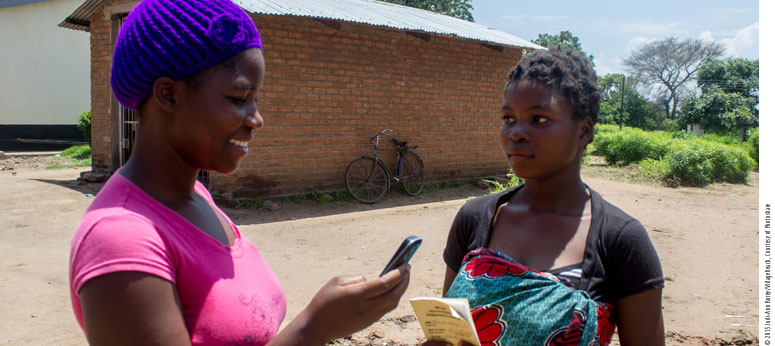 two women talking about family planning one is holding a phone in a rural area